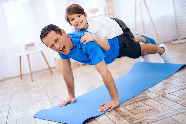 Tired man with child on back wrung out from floor. Premium Photo
