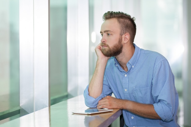 Tired manager looking at window in office Free Photo