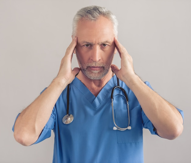 Tired mature doctor in blue medical wear Premium Photo