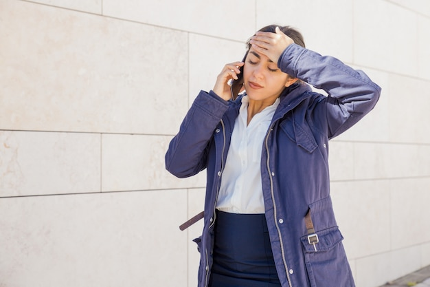 Tired office girl speaking on mobile phone Free Photo