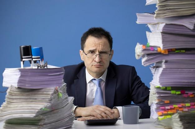 Усталый офисный работник гримасничает, в окружении документов Premium Фотографии