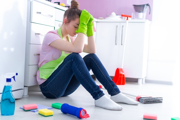 Tired overworked cleaning woman feeling fatigue of busy day and cleaning house at kitchen at home Premium Photo