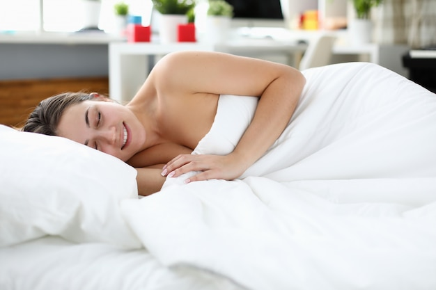 Усталый человек под белым пуховым одеялом Premium Фотографии