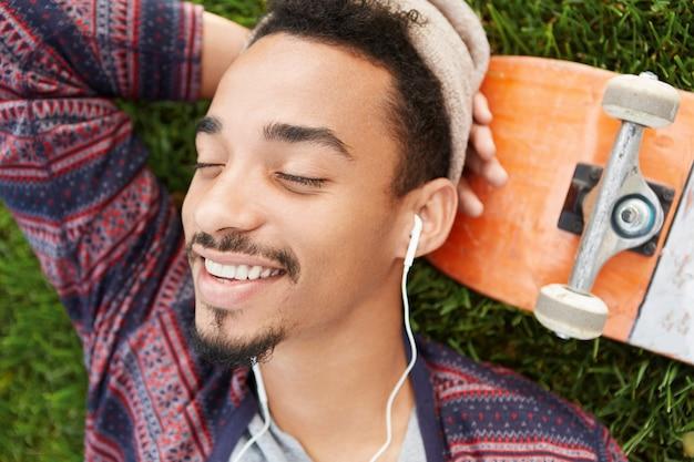 Il giovane pattinatore di talento e soddisfatto stanco fa un sonnellino sul prato verde, sorride felice mentre vede sogni piacevoli Foto Gratuite
