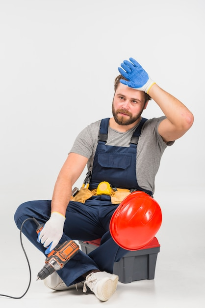 Tired repairman sitting with drill on tool box Free Photo