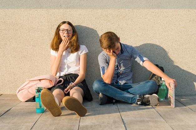本、バックパックと灰色の壁で外に座って疲れている学童10代 Premium写真