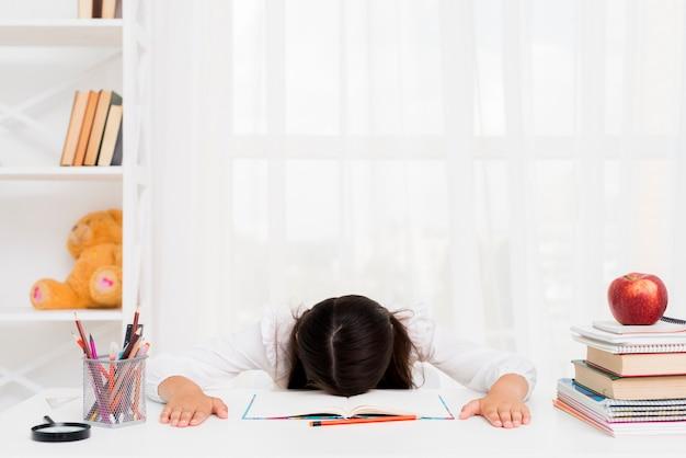Tired schoolgirl lying over copybook Free Photo