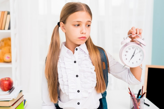 Tired schoolgirl with backpack holding clock in classroom Free Photo