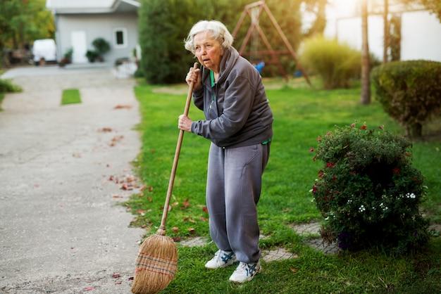 家の裏庭でほうきを持って疲れている年配の女性。 Premium写真