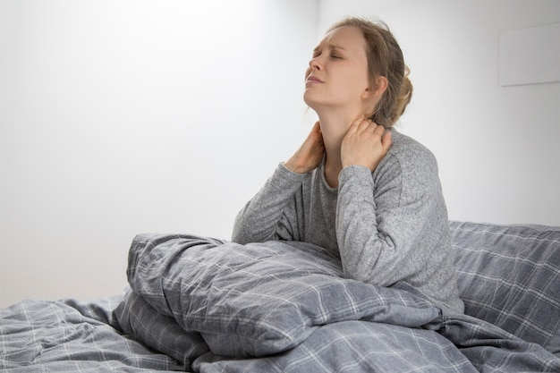 Tired sick woman on bed touching her neck, suffering from pain Free Photo