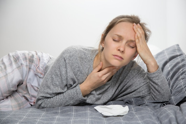 Tired sick woman in bed with closed eyes having sore throat Free Photo