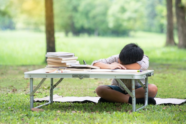 Tired sleeping asian child while reading book in park Premium Photo
