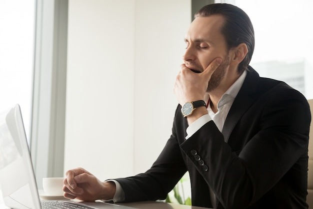 Tired sleepy businessman yawning in front of laptop Free Photo
