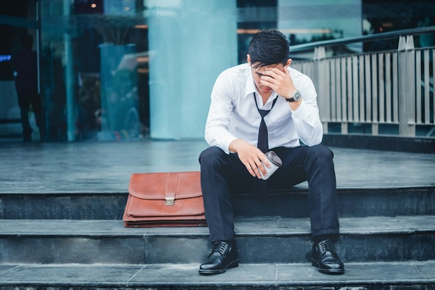 Tired or stressed businessman sitting on the walkway Premium Photo