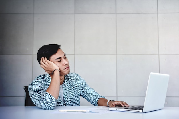 Tired and stressed young businessman sitting on desk in office with computer Premium Photo
