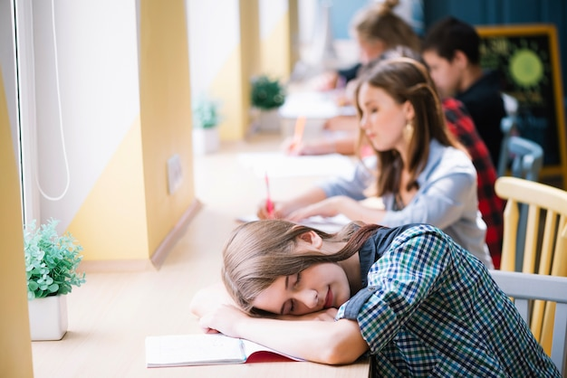 Tired student sleeping on notepad Free Photo