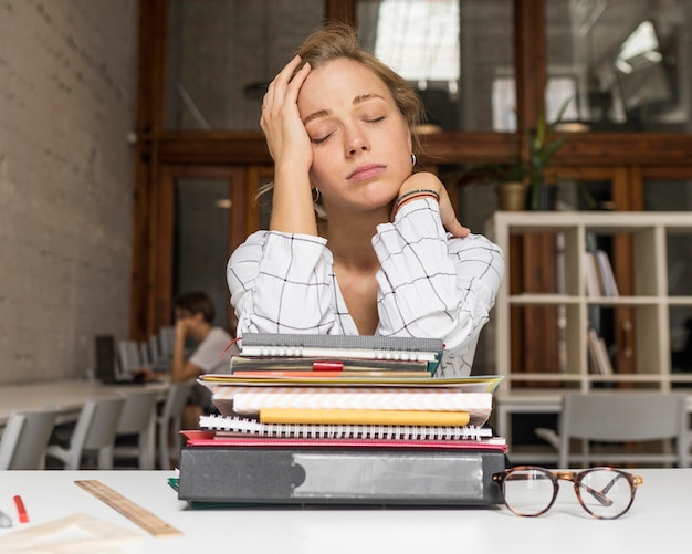 Tired teacher with stack of books on desk Free Photo