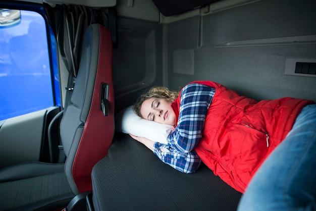 Усталый водитель грузовика спит в кабине своего грузовика из-за езды на большие расстояния и переутомления Бесплатные Фотографии