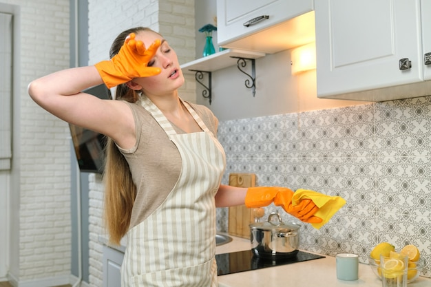 Tired woman in apron gloves doing house cleaning in the kitchen Premium Photo