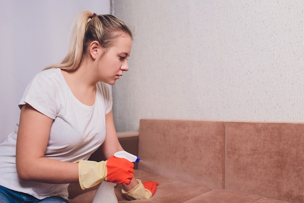 Tired woman cleaning sofa Premium Photo