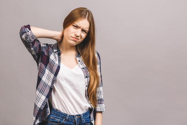 Утомленная женщина имея лоток в шеи изолированной против серой стены. Premium Фотографии