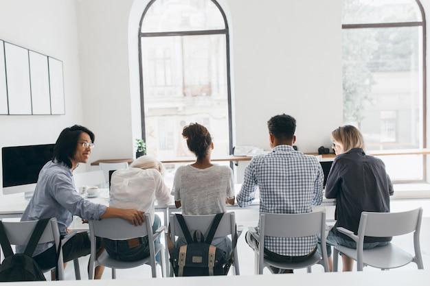 仕事の会議中にアジア人男性とアフリカ人女性の間に座っている白いシャツの疲れた女性。講義の後、大学のホールでリラックスしているアジアの学生と彼の友人の後ろからの屋内の肖像画。 無料写真