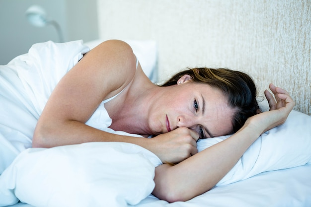 Tired woman lying in her bedroom on her bed Premium Photo