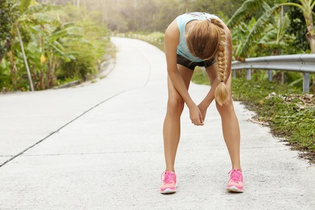 Усталая женщина-бегун отдыхает после тяжелого пробега по дороге в лесу, наклонившись вперед, положив локти на колени. Бесплатные Фотографии