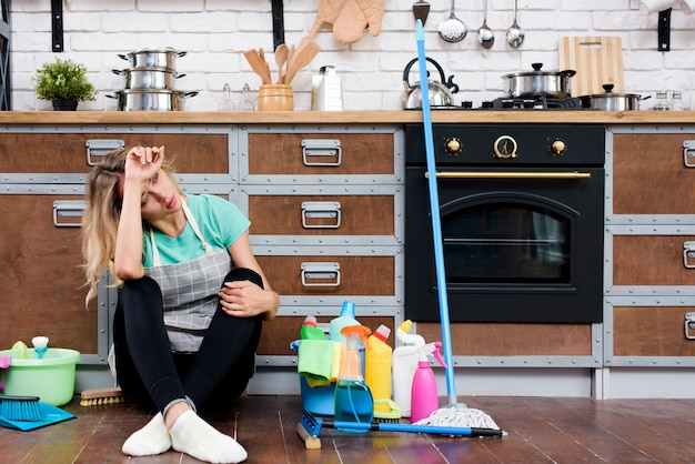 Tired woman sitting on kitchen floor with cleaning products and equipment Free Photo