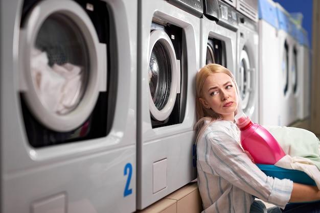 洗濯機の近くに座って悲しそうに見上げる疲れた女性。白人女性は、バスケットに汚れた服を着て、洗濯、待機、退屈な女性に時間を費やしました Premium写真