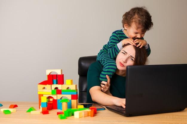 Усталая женщина с ребенком на шее сидит за компьютером и разговаривает по телефону с работодателем, пока ребенок играет в кубики и висит вокруг нее. Premium Фотографии