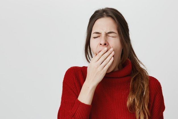 Tired woman yawning, cover opened mouth Free Photo
