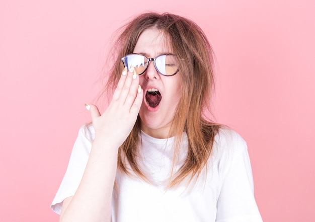 손으로 입을 벌리고 하품하는 피곤한 여자는 휴식이 필요합니다. 머리가 졸린 젊은 여성 노동자는 불면증으로 깨어날 수 없습니다. 프리미엄 사진