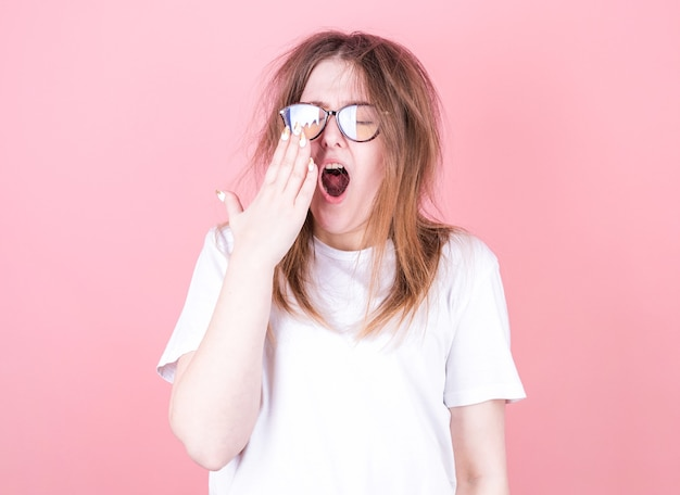 Tired woman yawning covering open mouth with hand need rest. young female worker being sleepy head can't wake up having insomnia. Premium Photo