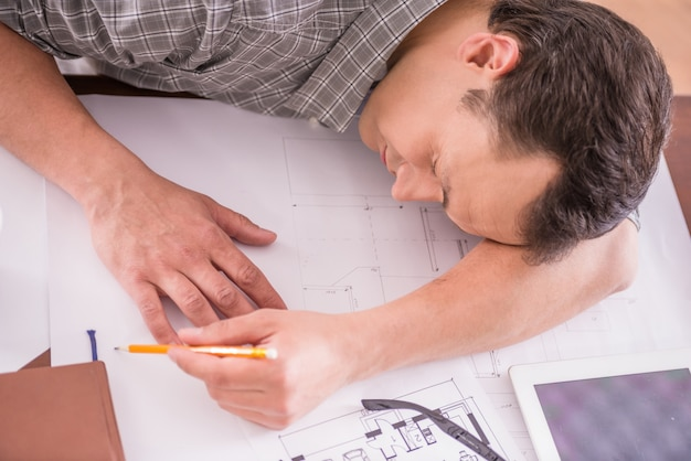 Tired working man sleeping at workplace full of sketches. Premium Photo