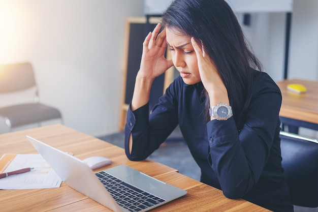 Tired working woman with headache at office. Premium Photo