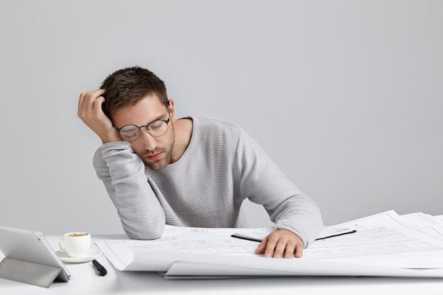 Stanco giovane uomo attraente dorme sul posto di lavoro, ha molto lavoro, è affaticato ed esausto Foto Gratuite