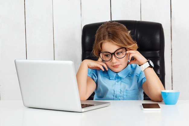 Giovane bella ragazza stanca che si siede al posto di lavoro in ufficio. Foto Gratuite