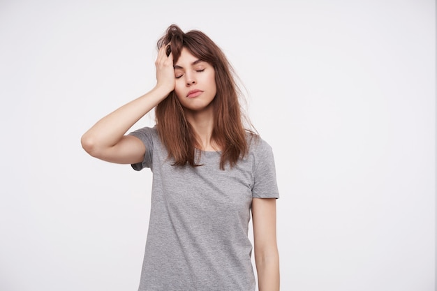 Tired young brown haired woman keeping her eyes closed and holding raised palm on head while posing on white in grey basic t-shirt Free Photo