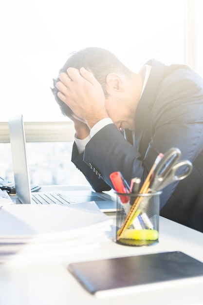 Tired young businessman with laptop at his workplace Free Photo