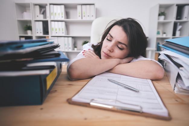 Усталая молодая женщина-офис-менеджер или бухгалтер дремлет на столе перед буфером обмена с финансовыми бумагами после тяжелого рабочего дня Premium Фотографии