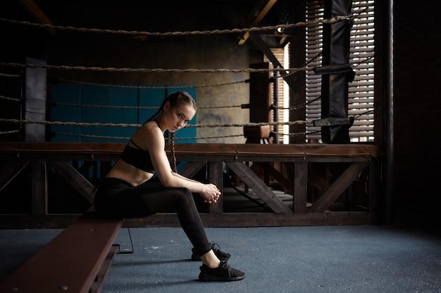 Stanco giovane femmina con corpo slim fit seduto sulla panchina dopo l'allenamento di boxe nella moderna palestra, indossando abiti sportivi neri e scarpe da ginnastica Foto Gratuite
