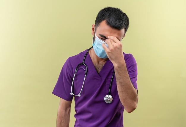 紫色の外科医の服と聴診器の医療マスクを身に着けている疲れた若い男性医師は、孤立した緑の壁の額に手を置きました 無料写真