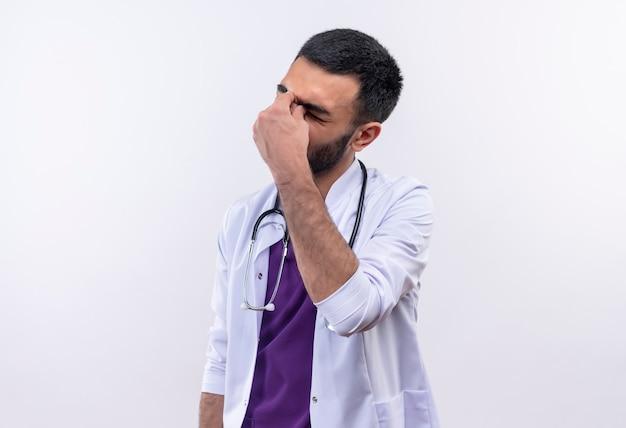 聴診器の医療用ガウンを身に着けている疲れた若い男性医師は、孤立した白に彼の手を置きます 無料写真