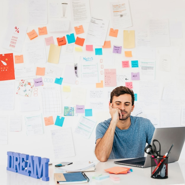 Tired young man sitting near laptop against wall with notes Free Photo