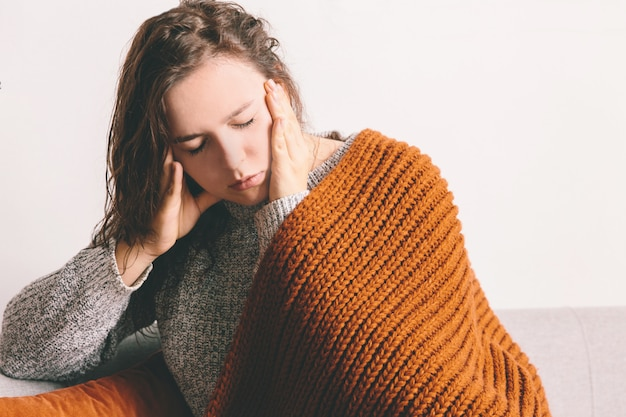 Tired young woman lying on the sofa on white wall background. headache Premium Photo