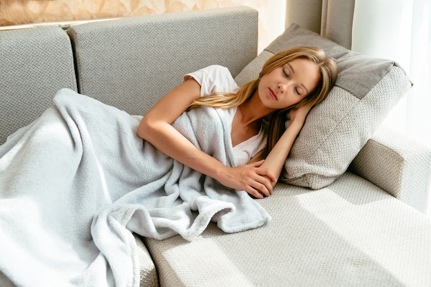 Tired young woman sleeping on sofa in living room at home. leisure concep Free Photo
