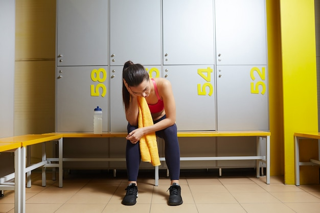Tiredness woman in lockers room Free Photo