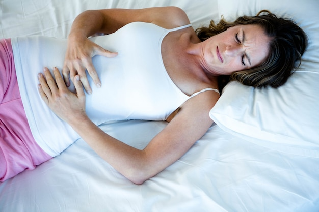 Tiredwoman lying in her  bed clutching her stomach Premium Photo