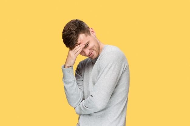 Усталый молодой человек с эмоциями головной боли на желтом фоне Бесплатные Фотографии